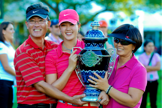 Michelle Wie wins her first career at LPGA tournament  Ochoa_holding her trophy with her family daddy and mommy.PNG