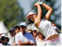 Michelle Wie in white and pink finishing off a swing.PNG